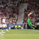 Alisson Becker saves a Christian Eriksen free kick